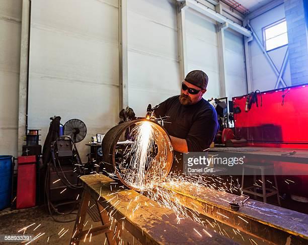 Welder working in metal workshop