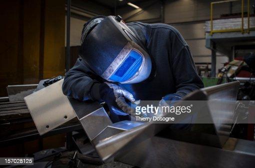 Welder working in metal worshop : Stock Photo