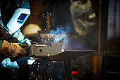 Welder working in steel manufacturing facility