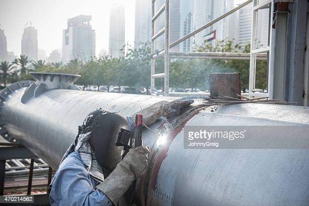 Welder working on steel pipe