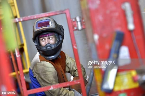 A welder works at the site of French shipyard STX in SaintNazaire western France on September 28 2017 Italian shipbuilder Fincantieri will take...