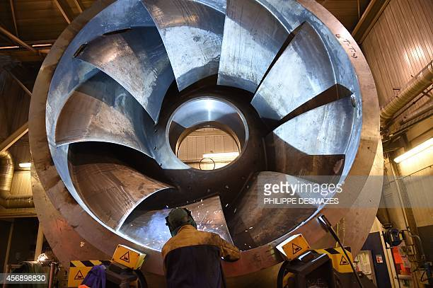 A welder works on a pumpturbine at the Alstoms global technology and hydropower centre in Grenoble eastern France on October 8 2014 The centre which...