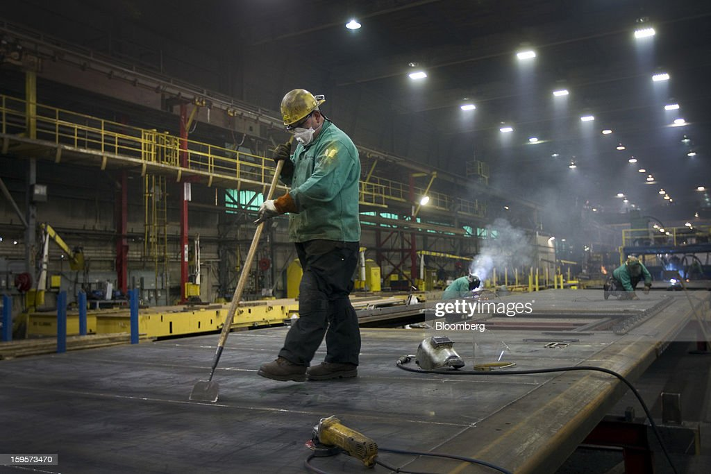 A welder works on sides for refrigerated railcars at the Greenbrier Cos.' Gunderson railcar plant in Portland, Oregon, U.S., on Tuesday, Jan. 15, 2013. Industrial production in the U.S. climbed for a second month in December as demand picked up for capital equipment, showing factories strengthened entering 2013. Photographer: Natalie Behring/Bloomberg via Getty Images