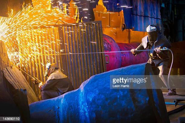 Welders at work in steel forge