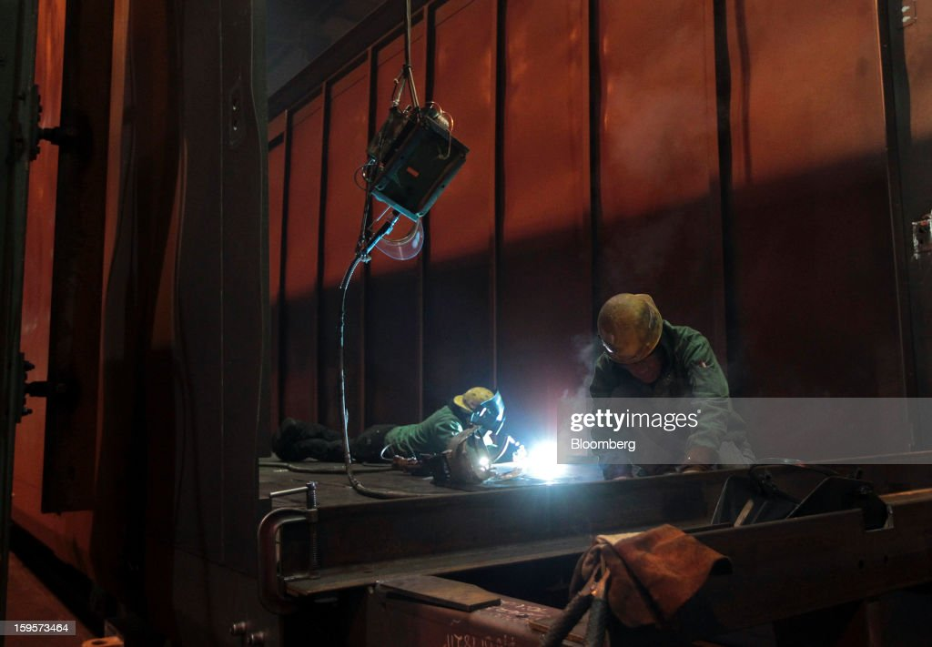 Welders work on a refrigerated railcar at the Greenbrier Cos.' Gunderson railcar plant in Portland, Oregon, U.S., on Tuesday, Jan. 15, 2013. Industrial production in the U.S. climbed for a second month in December as demand picked up for capital equipment, showing factories strengthened entering 2013. Photographer: Natalie Behring/Bloomberg via Getty Images