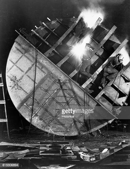 Welders work on hull of new submarine at Electric Boat Co Groton Conn August 1943