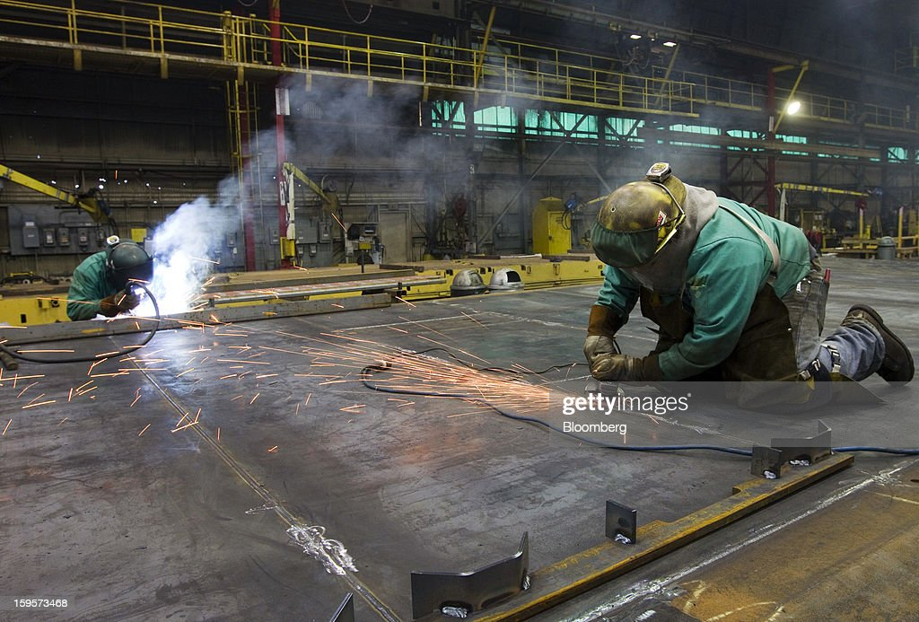 Welders work on sides for refrigerated railcars at the Greenbrier Cos.' Gunderson railcar plant in Portland, Oregon, U.S., on Tuesday, Jan. 15, 2013. Industrial production in the U.S. climbed for a second month in December as demand picked up for capital equipment, showing factories strengthened entering 2013. Photographer: Natalie Behring/Bloomberg via Getty Images