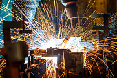 Welding robots movement in a car factory (manufacturing, industry, factory)