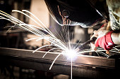 Worker welding steel in company.