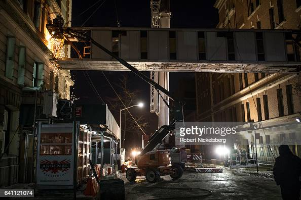 A welding team cuts the support beams to a 17ton pedestrian bridge before a crane removes the span between the historic landmarked Polhemus Building...