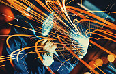 Unrecognizable man welding metal plate and construction frame. This is arc welding.The worker is using protective mask and blue working uniform. Background is lit orange. Long exposure.