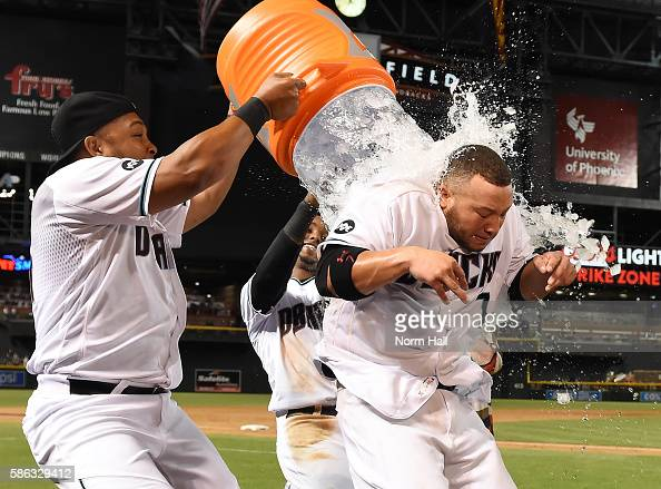 Welington Castillo of the Arizona Diamondbacks has a cooler of ice water dumped over him by teammates Yasmany Tomas and Jean Segura after a 32 win...