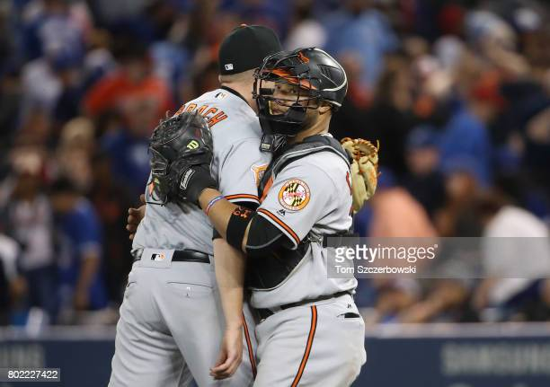Welington Castillo of the Baltimore Orioles celebrates their victory with Brad Brach during MLB game action against the Toronto Blue Jays at Rogers...