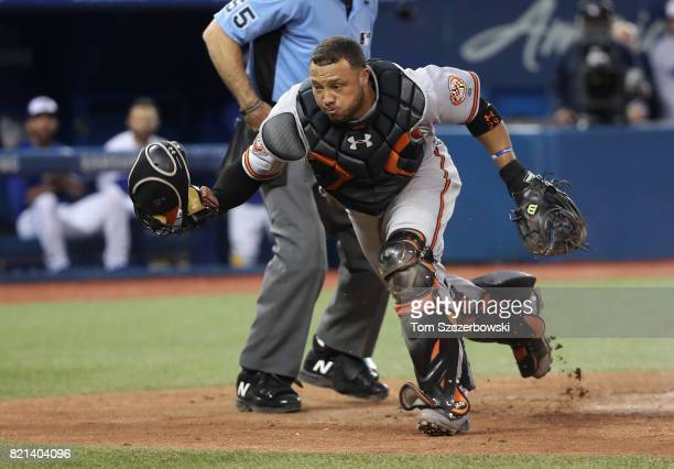 Welington Castillo of the Baltimore Orioles chases a pitch that got away from him but Jose Bautista of the Toronto Blue Jays could not score on the...
