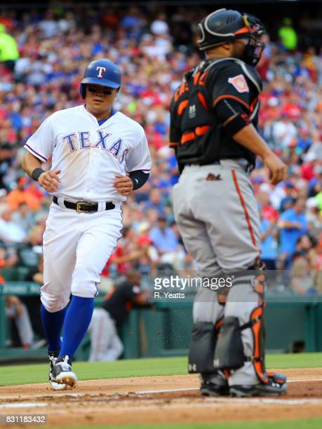 Welington Castillo of the Baltimore Orioles looks on as ShinSoo Choo of the Texas Rangers scores in the first inning at Globe Life Park in Arlington...