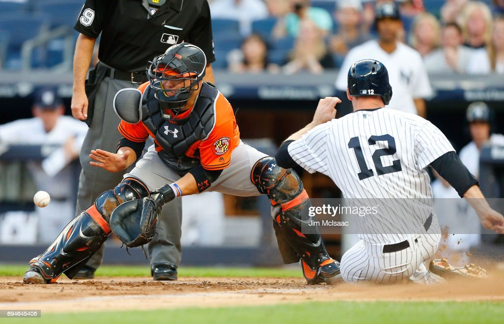 Welington Castillo #29 of the Baltimore Orioles waits for the throw as Chase Headley #12 of the New York Yankees slides home with a run in the first inning at Yankee Stadium on June 10, 2017 in the Bronx borough of New York City.