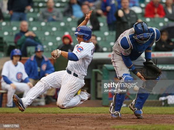 Welington Castillo of the Chicago Cubs slides in to score a run in the 5th inning as AJ Pierzynski of the Texas Rangers drfops the ball at Wrigley...