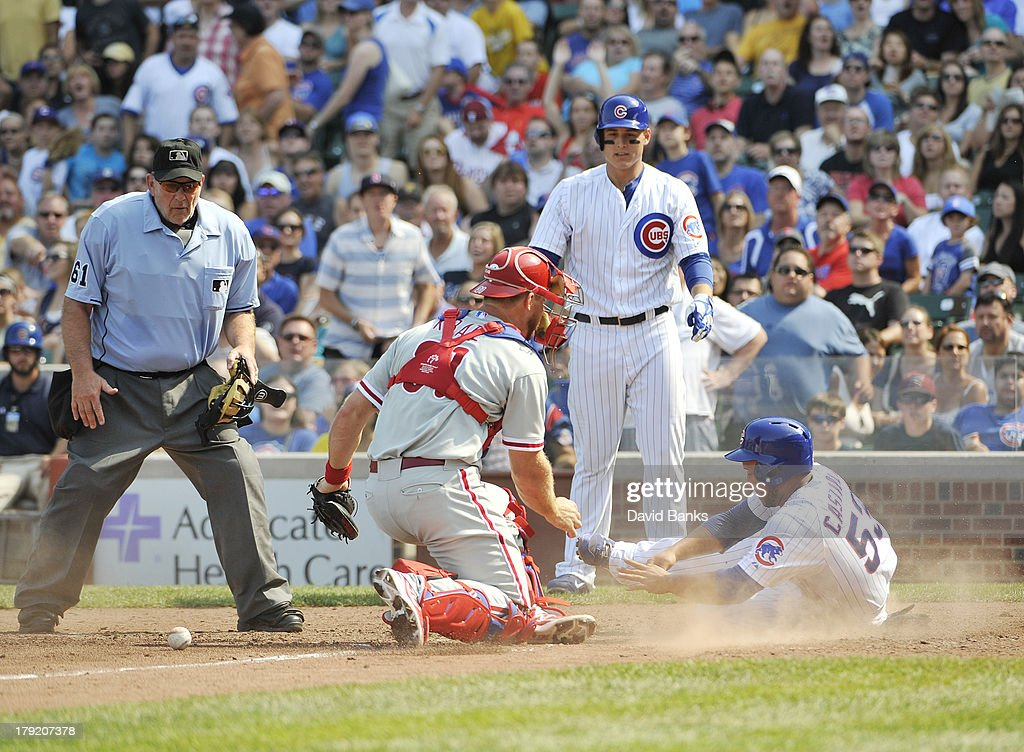 Welington Castillo #53 of the Chicago Cubs slides safely into home as Erik Kratz #31 of the Philadelphia Phillies can't handle the throw during the fourth inning on September 1, 2013 at Wrigley Field in Chicago, Illinois.