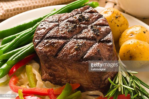 A well cooked filet of Mignon served with asparagus