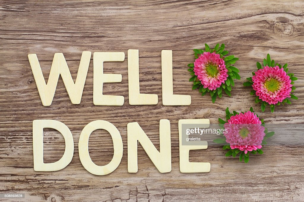 Well done written with wooden letters and pink daisy flowers : Stock Photo