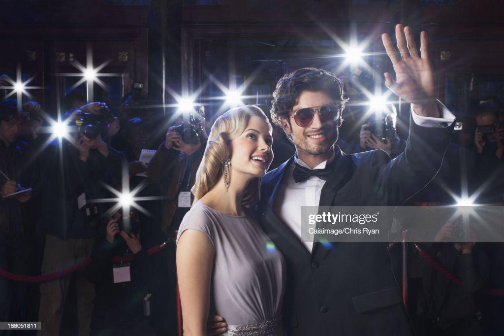 Gut gekleideten Stars paar winken paparazzi : Stock-Foto