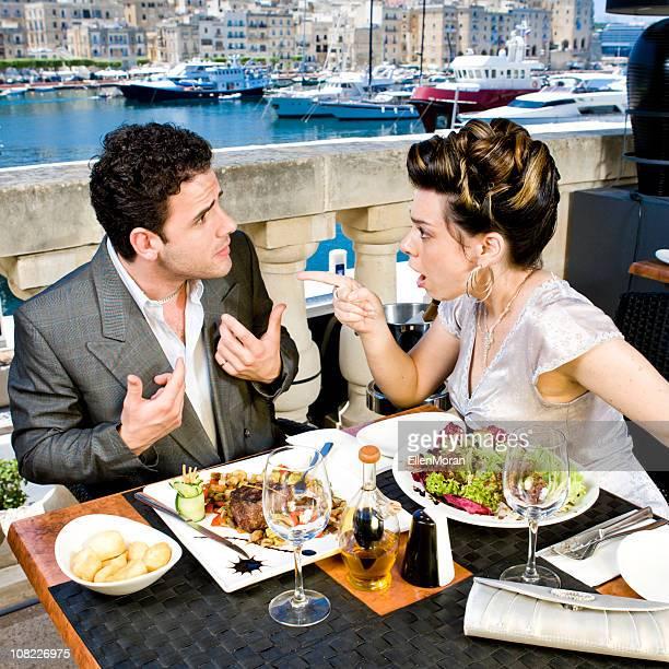 Gut gekleidete paar streiten über Abendessen am Dock