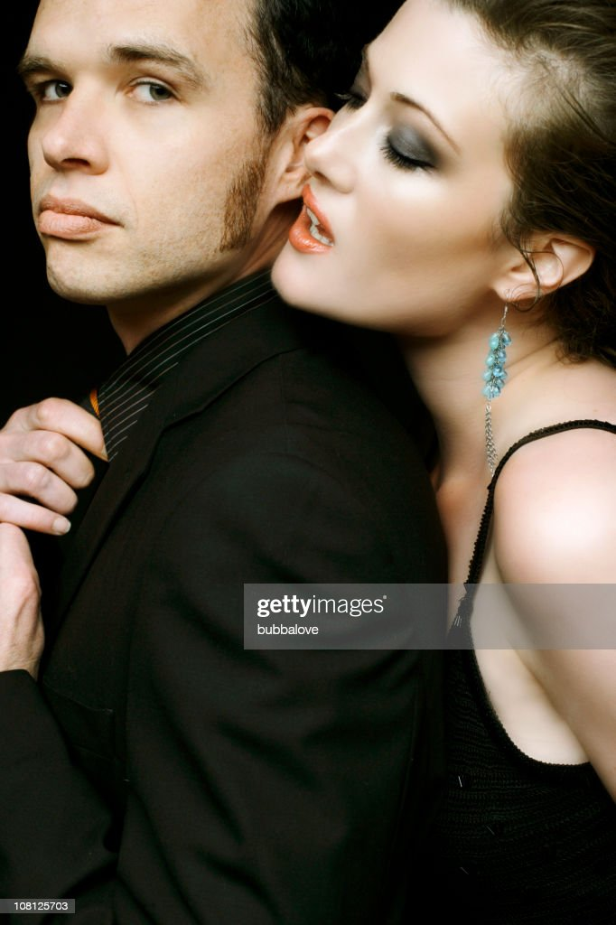 Well Dressed Couple Posing, Woman Whispering in Man's Ear : Stock Photo