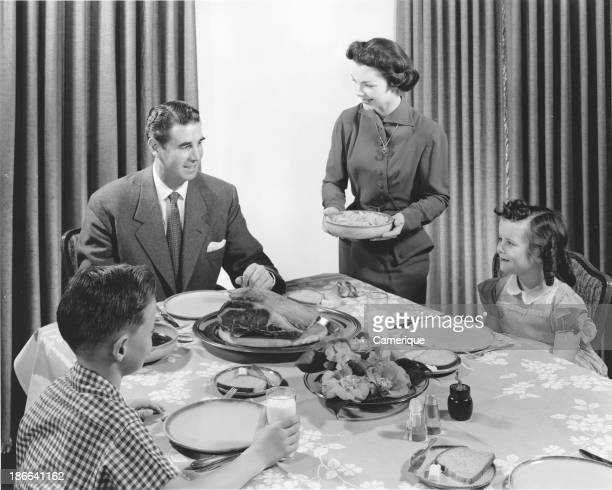 Well dressed family sitting down to a Thanksgiving dinner while Mom serves November 25 1955