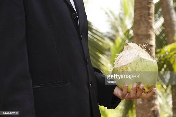 A well dressed man holding a coconut