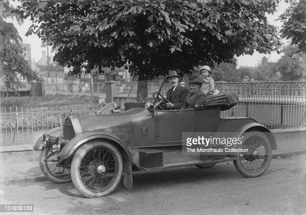 Well dressed man sitting in the driving seat of an open top motorcar with a lady and child passengers parked alongside railings by a river circa 1917