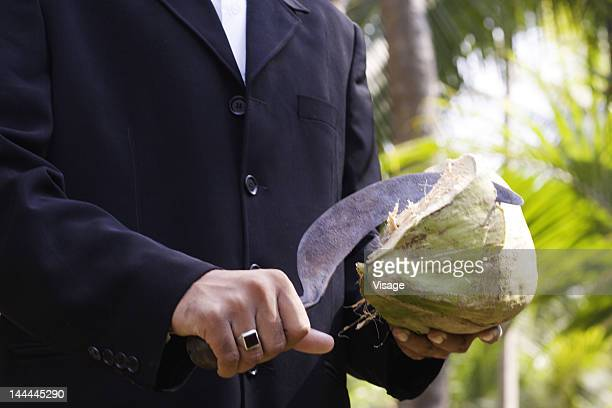 A well dressed man using a sickle to cut open a coconut