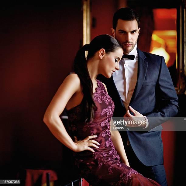 Bien habillés sensuel couple posant à l'intérieur