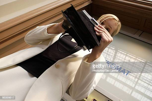 Well dressed woman looking through purse, low angle view