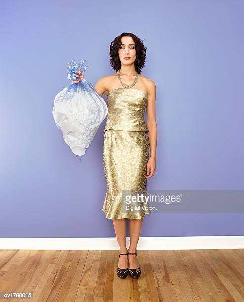 Well Dressed Woman Standing Holding a Bin Bag