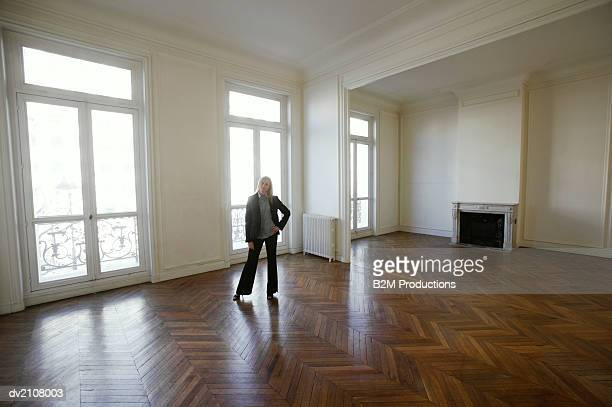 Well Dressed Woman Standing in a Large Empty Room with a Wooden Floor