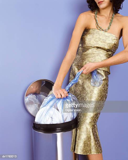 Well Dressed Woman Tying Up a Bin Bag
