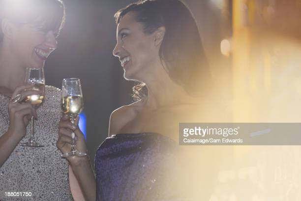Well dressed women drinking champagne in luxury bar