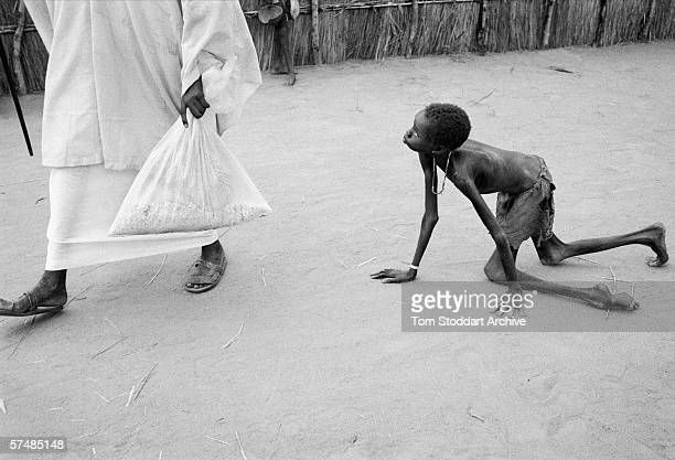A well nourished Sudanese man steals maize from a starving child during a food distribution at Medecins Sans Frontieres feeding centre at Ajiep...