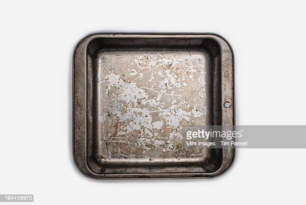 A well used, seasoned baking tray. Cookware. A square baking cake tin 9 inches square. Pan.