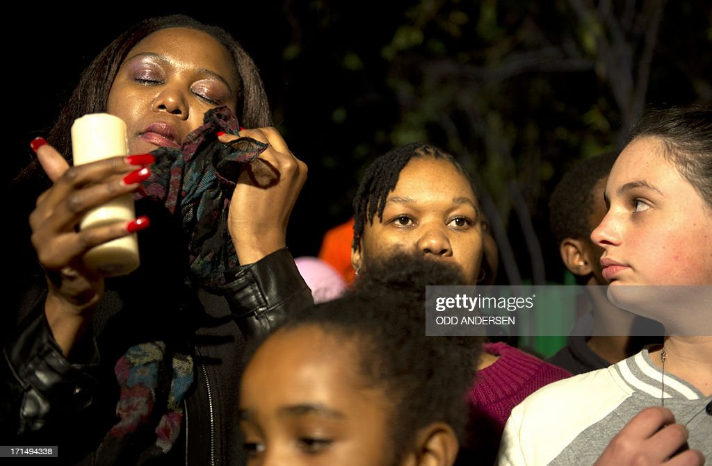 A well wisher (L) wipes a tear during a candle lit vigil outside the Mediclinic Heart Hospital in Pretoria where a community group prayed and sang religious songs in support of Nelson Mandela who is receiving treatment there, on June 25, 2013. Mandela's close family gathered today at his rural homestead to discuss the failing health of the South African anti-apartheid icon who was fighting for his life in hospital. Messages of support poured in from around the world for the Nobel Peace Prize winner, who spent 27 years behind bars for his struggle under white minority rule and went on to become South Africa's first black president. AFP PHOTO / ODD ANDERSEN