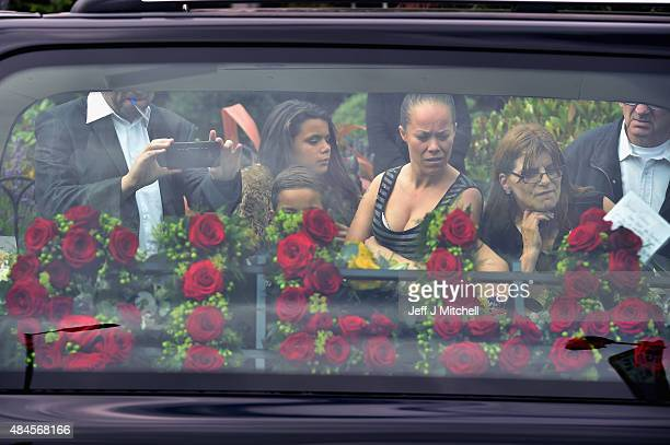 Well wishers gather around a funeral car with a floral tribute spelling 'Cilla' in red roses before the hearse leaves funeral director's B Jenkins...