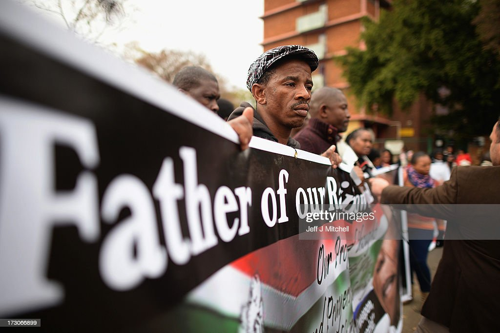 Well wishers hold banners as they gather to pay tribute to former South African President Nelson Mandela at the memorial wall at the Medi-Clinic Heart Hospital on July 6, 2013 in Pretoria, South Africa. Mandela has been hospitalized at the Medi-Clinic Hospital since June 8, to receive treatment for a recurring lung infection.