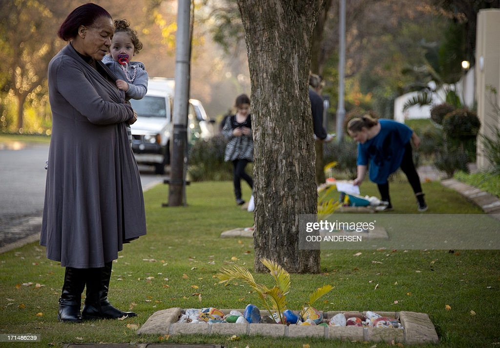 Well wishers place painted stones with messages and flowers outside former South African President Nelson Mandela's residence in Johannesburg on June 25, 2013. Mandela is receiving treatment at the Mediclinic heart hospital in Pretoria. Mandela's close family gathered today at his rural homestead to discuss the failing health of the South African anti-apartheid icon who was fighting for his life in hospital. Messages of support poured in from around the world for the Nobel Peace Prize winner, who spent 27 years behind bars for his struggle under white minority rule and went on to become South Africa's first black president.