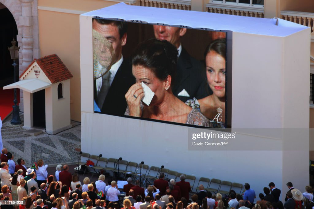 Well wishers watch on the big screen <a gi-track='captionPersonalityLinkClicked' href=/galleries/search?phrase=Princess+Stephanie+of+Monaco&family=editorial&specificpeople=171100 ng-click='$event.stopPropagation()'>Princess Stephanie of Monaco</a> as she attends the civil ceremony of the Royal Wedding of <a gi-track='captionPersonalityLinkClicked' href=/galleries/search?phrase=Prince+Albert+II+of+Monaco&family=editorial&specificpeople=201707 ng-click='$event.stopPropagation()'>Prince Albert II of Monaco</a> to <a gi-track='captionPersonalityLinkClicked' href=/galleries/search?phrase=Charlene+-+Princess+of+Monaco&family=editorial&specificpeople=726115 ng-click='$event.stopPropagation()'>Charlene</a> Wittstock at the Prince's Palace on July 1, 2011 in Monaco. The ceremony took place in the Throne Room of the Prince's Palace of Monaco, followed by a religious ceremony to be conducted in the main courtyard of the Palace on July 2. With her marriage to the head of state of Principality of Monaco, <a gi-track='captionPersonalityLinkClicked' href=/galleries/search?phrase=Charlene+-+Princess+of+Monaco&family=editorial&specificpeople=726115 ng-click='$event.stopPropagation()'>Charlene</a> Wittstock will become Princess consort of Monaco and gain the title, Princess <a gi-track='captionPersonalityLinkClicked' href=/galleries/search?phrase=Charlene+-+Princess+of+Monaco&family=editorial&specificpeople=726115 ng-click='$event.stopPropagation()'>Charlene</a> of Monaco. Celebrations including concerts and firework displays are being held across several days, attended by a guest list of global celebrities and heads of state.