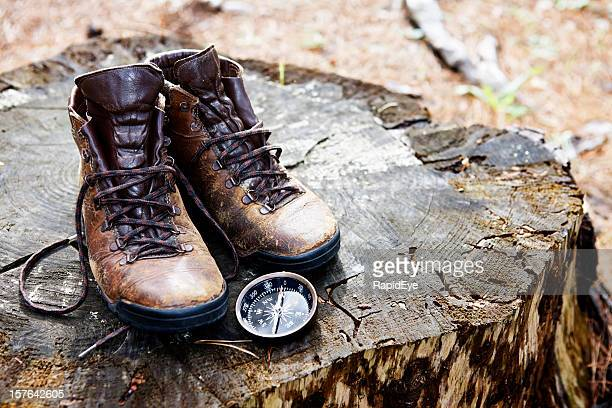 ABGETRAGENES Wanderschuhe mit Kompass auf Baumstumpf