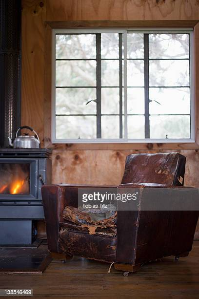 A well worn leather armchair next to a wood burning stove