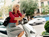 Well-Dressed Businesswoman Sits on Her Parked Motor Scooter in the City, Using Her Mobile Phone