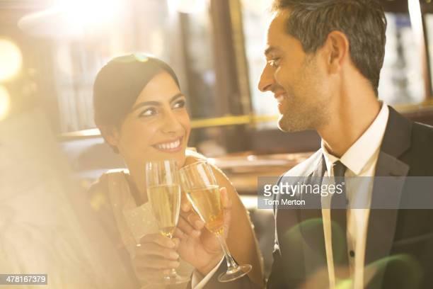 Gut gekleidete paar Anstoßen mit Champagner Flöten im restaurant