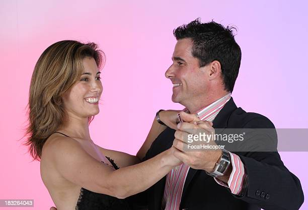 Well-dressed dancing couple smiling at each other