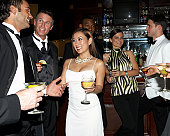 Well-dressed men and women with cocktails in bar